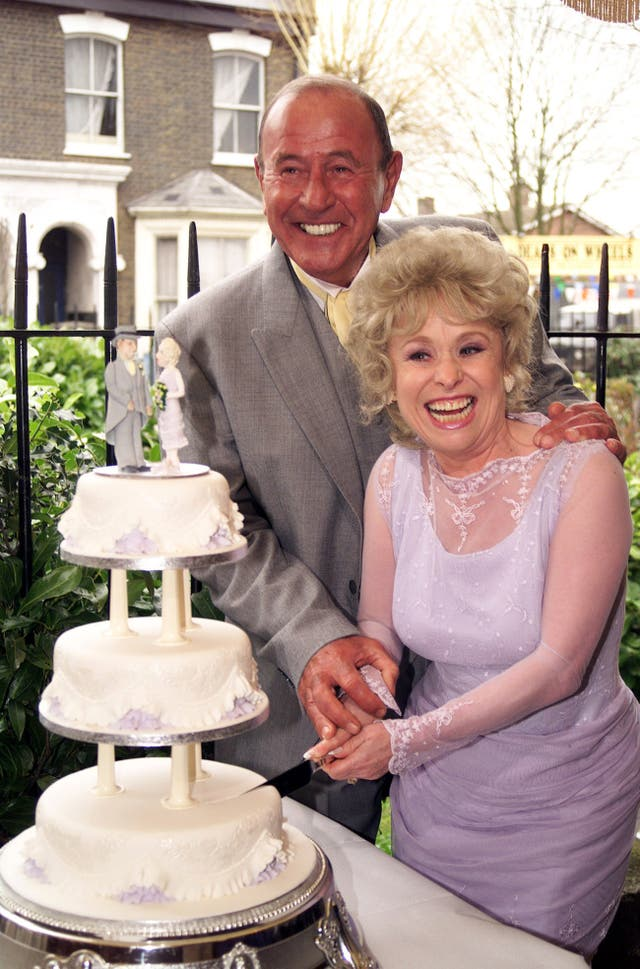 Peggy Mitchell and Frank Butcher (Mike Reid) cutting their cake