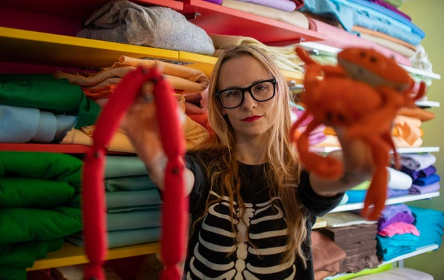 Lucy Sparrow in her workshop with some of her felt art pieces (Joe Giddens/PA)