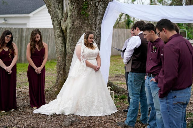Emily Pascale takes her wedding vows with Taylor Pascale, outside the home of Taylor's parents in Grand Lake, Louisiana