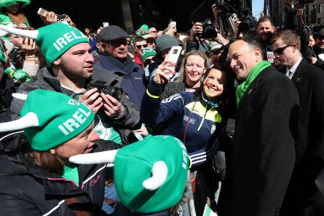 The Taoiseach poses for selfies with people watching the parade (Niall Carson/PA)