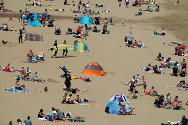 People enjoy the sunshine on Tynemouth beach (Owen Humphreys/PA)