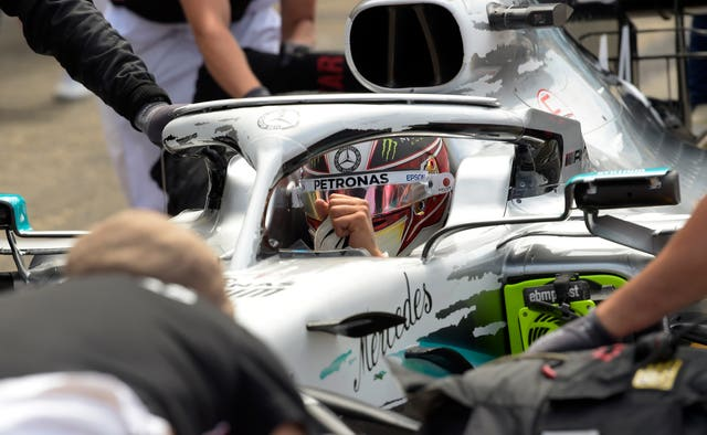 Pit crew work on the car of Mercedes driver Lewis Hamilton