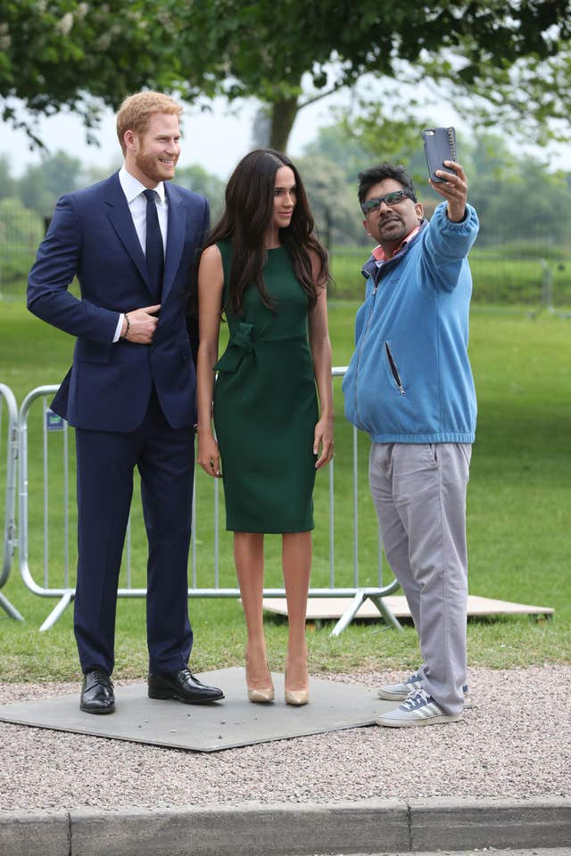 A royal fan takes a selfie with the Madame Tussauds' figures of Harry and Meghan along the Long Walk in Windsor (Jonathan Brady/PA)