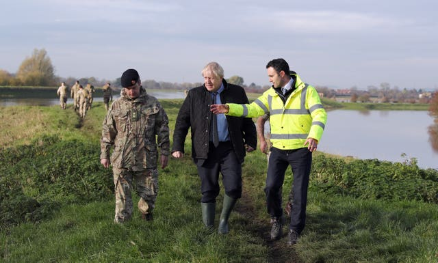 Prime Minister Boris Johnson walks with Lt Col Tom Robinson from the Light Dragoons and an Environment Agency official during a visit to Stainforth, Doncaster, to see the recent flooding