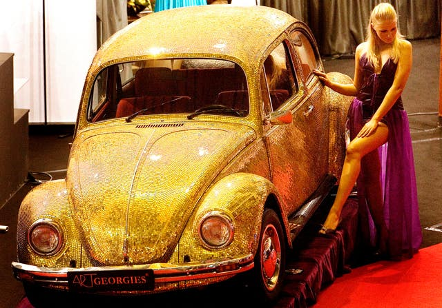 A model poses next to a 1968 Volkswagen Beetle covered in tiles made of a blend of 18 karat gold and glass at the annual Luxury Show in Bucharest, Romania