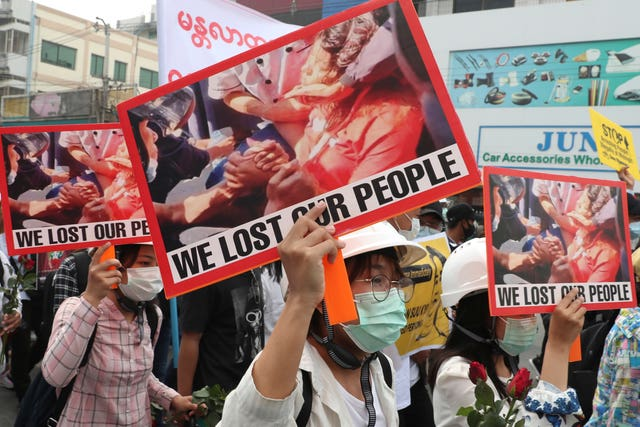 Anti-coup protesters hold an image of Mya Thwet Thwet Khine with a sign that reads We Lost Our People during an anti-coup protest rally in Mandalay, Myanmar