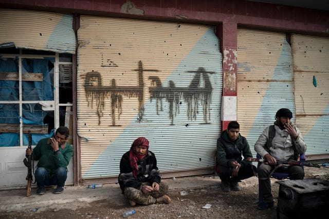 US-backed forces sit outside a building as the fight against Islamic State continues in the village of Baghouz in Syria