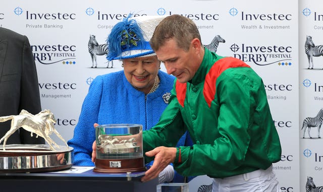 The Queen presents Pat Smullen with his Derby trophy following the victory of Harzand