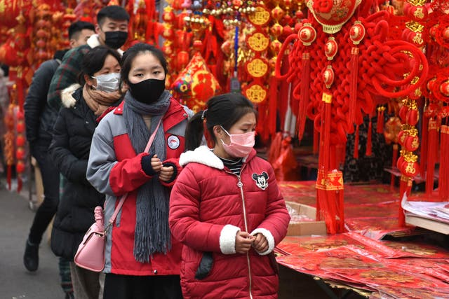 People wear face masks as they shop for decorations for the upcoming Lunar New Year, the Year of the Rat, at a market in Fuyang in central China's Anhui Province