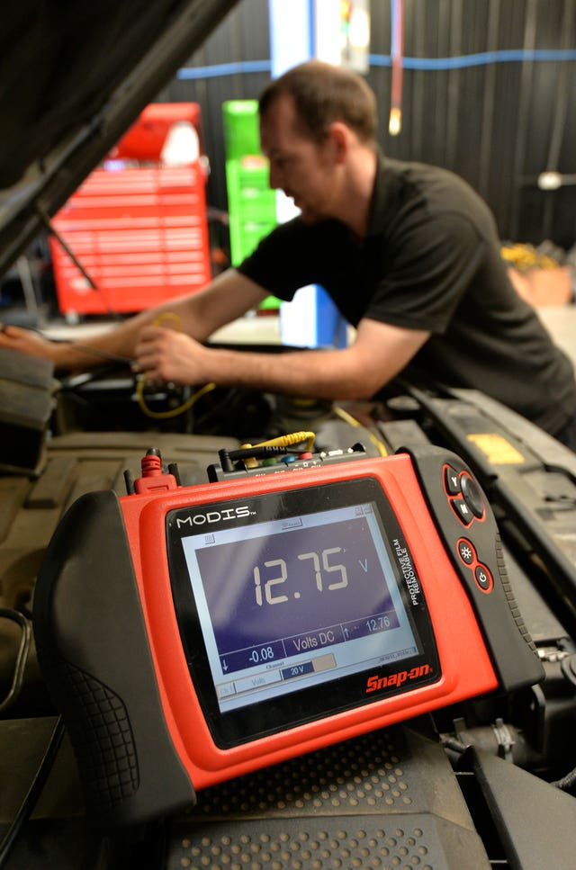 A mechanic checks the health of a car battery (Andrew Matthews/PA)
