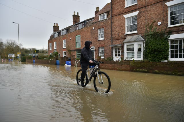 A cyclist negotiates the flood water in Tewkesbury (Ben Birchall/PA).