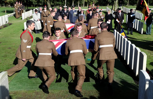 Soldiers prepare to bury two coffins during a burial service at the Commonwealth War Graves Commission's Wytschaete Military Cemetery, near Ypres