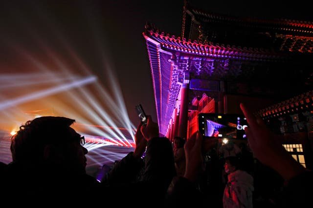 Visitors take photos of the Forbidden City illuminated with lights during the Lantern Festival in Beijing
