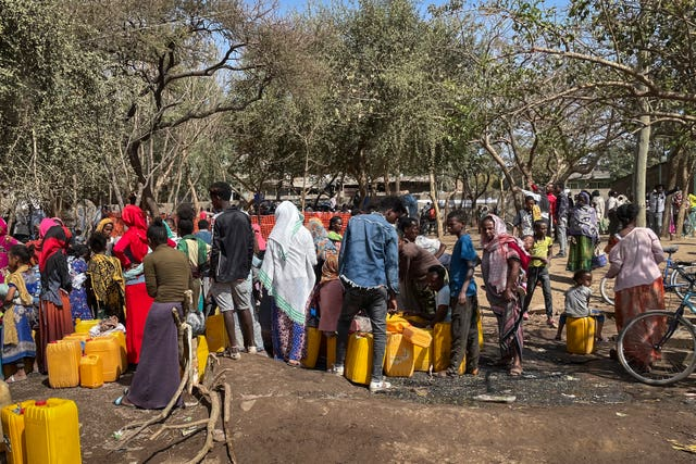 People displaced by the recent conflict gather around water point (AP)
