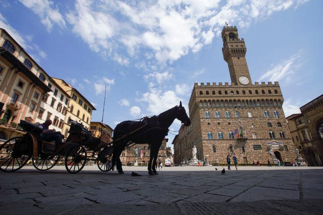 A horse-driven carriage waits for customers in an unusually uncrowded historical Piazza della Signoria square, in Florence (Andrew Medichini/AP)