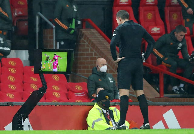 Referee David Coote consults the VAR before disallowing a penalty for West Brom