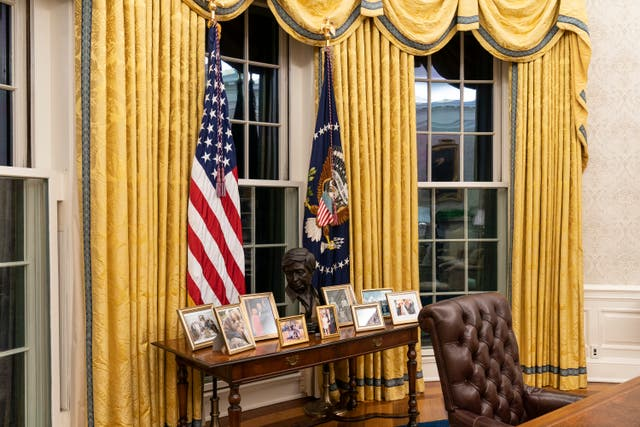 The Oval Office of the White House is newly redecorated for the first day of President Joe Biden's administration in Washington, including a table with family photos