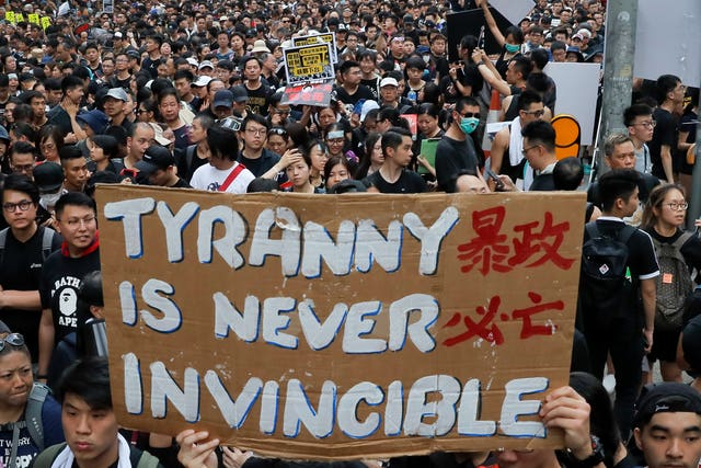 Tens of thousands of protesters carry posters and banners through the streets of Hong Kong