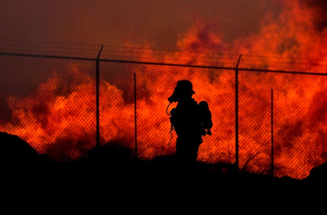 A firefighter walks past a wall of fire as multiple agencies battle a mulch and pallet fire burning out of control, fanned by Santa Ana winds
