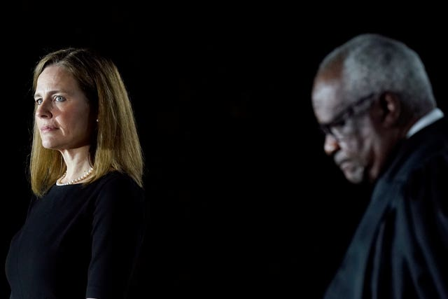 Amy Coney Barrett, left, and Supreme Court Justice Clarence Thomas listen as President Donald Trump speaks before Mr Thomas administers the Constitutional Oath to Ms Barrett on the South Lawn of the White House in Washington (Patrick Semansky/AP)