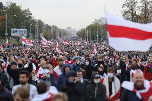 People with old Belarusian national flags march during an opposition rally