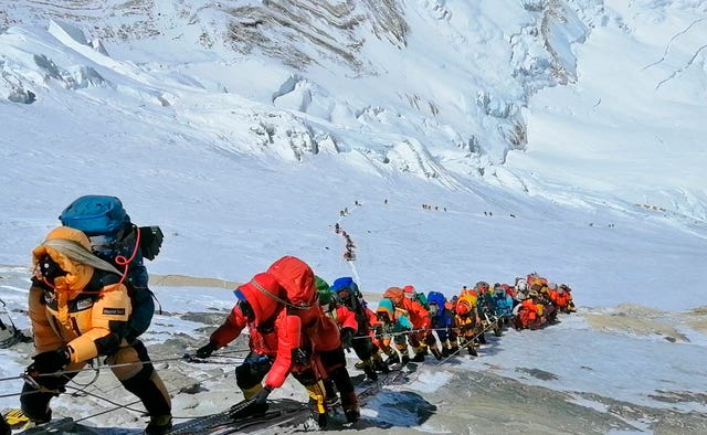 A queue of mountain climbers line a path on Mount Everest