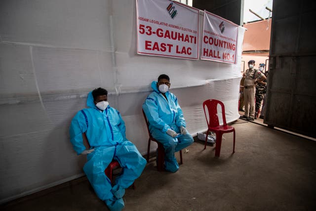 Counting agents in protective suits take a rest during the counting of votes for the Assam state assembly election in Gauhati, India