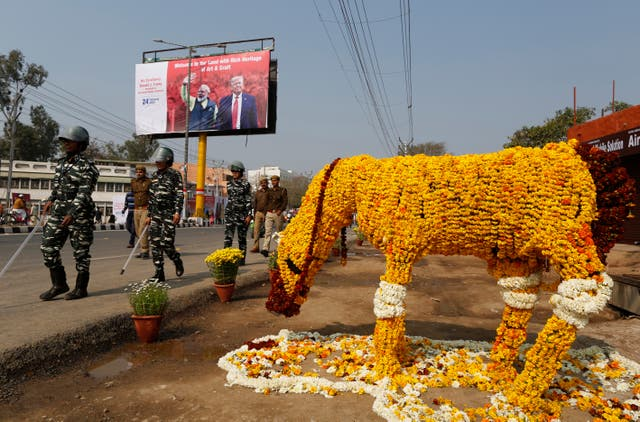 Security officers patrol on a street decorated with floral arrangements in Agra