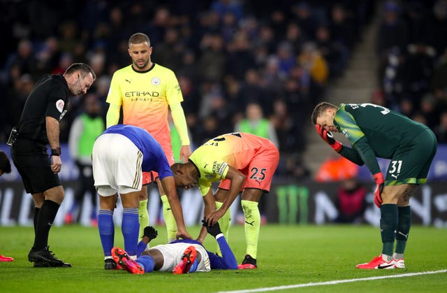 Leicester's Kelechi Iheanacho receives attention after a collision with Manchester City goalkeeper Ederson, right