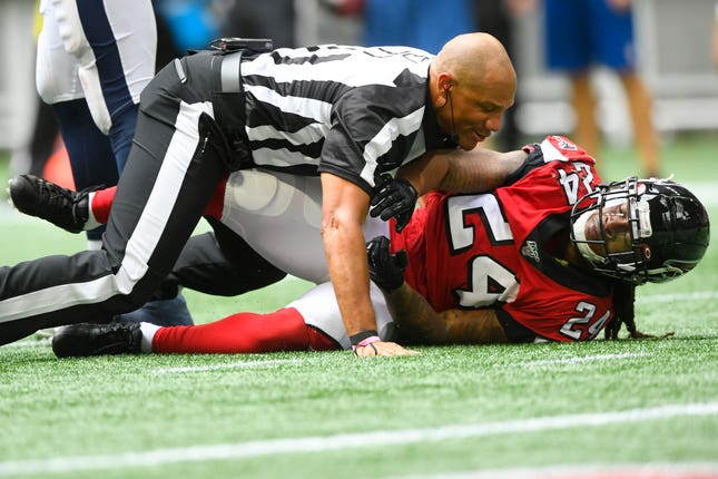 Devonta Freeman, right, is restrained by a referee
