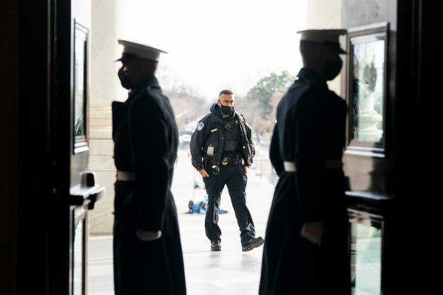White House Marine sentries and a US Capitol Police officer, centre, during a rehearsal for the 59th inaugural ceremony for President-elect Joe Biden and Vice President-elect Kamala Harris (Jim Lo Scalzo/AP)