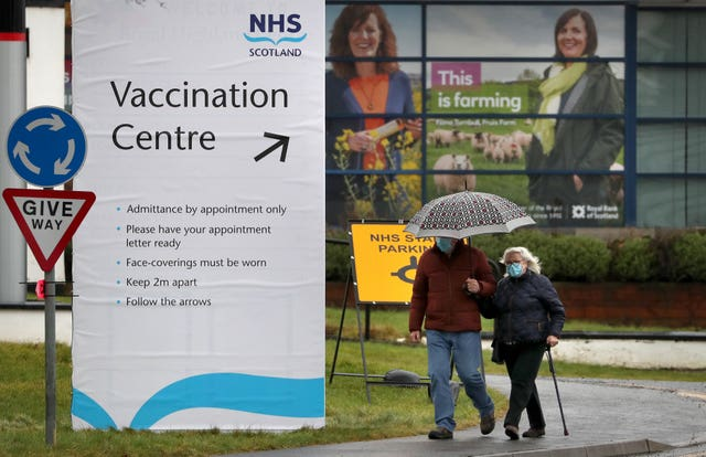 People walk passed a Vaccination Centre sign at the Royal Highland Show ground in Edinburgh