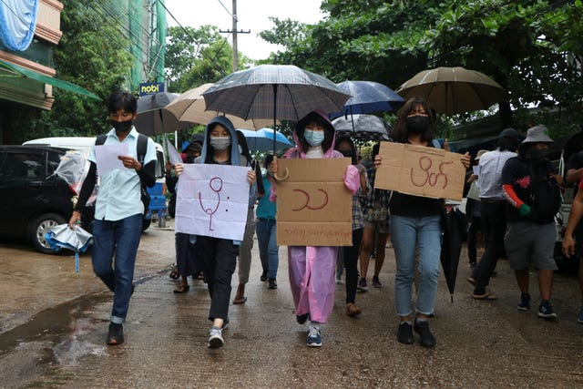 "Anti-coup protesters hold slogans which read ""Rain Strike"" as they use their umbrellas during a drizzle while participating in a demonstration in Yangon (AP)"