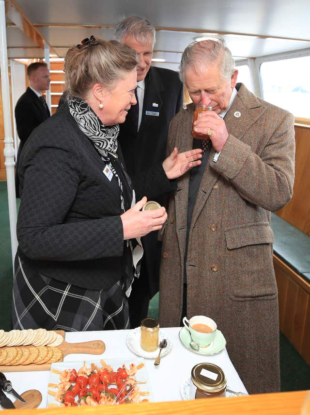 The Prince of Wales samples marmalade from Jane McCosh aboard the Lady Of The Lake, flagship vessel of the Ullswater Steamers company (Peter Byrne/PA)