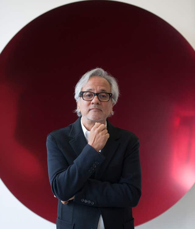 Artist Anish Kapoor in front of his work Mirror (Red) 2016