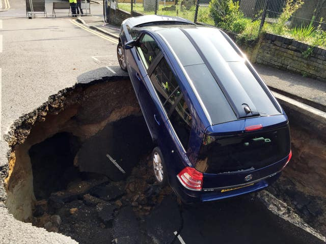 A car which has partially disappeared down a sinkhole in Woodland Terrace in Greenwich, south-east London