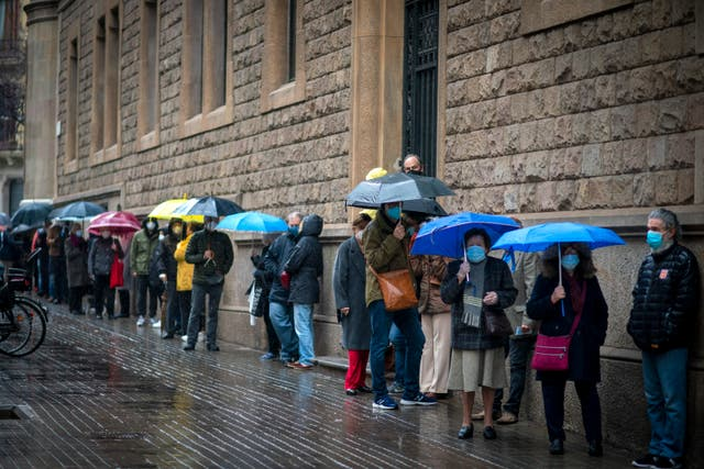 People line up to vote outside a polling station in Barcelona