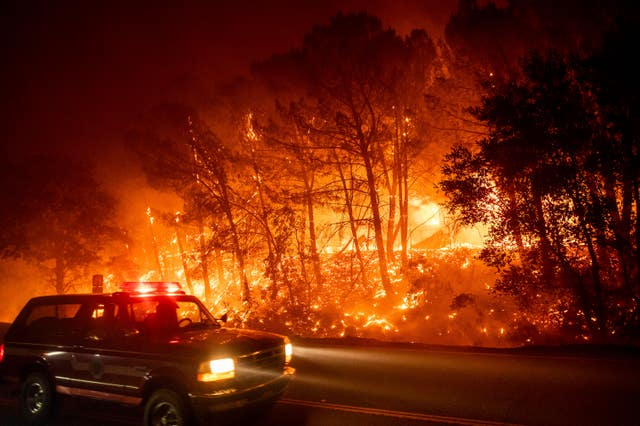 A fire vehicle passes burning trees on Pleasants Valley Road near Winters, California