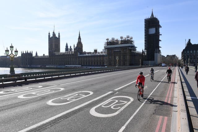 Cyclists ride across an empty Westminster Bridge