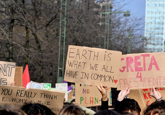 Demonstrators hold placards during a march for the climate in Brussels