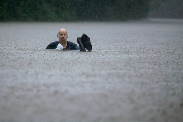 A man wades through floodwater in Patton Village