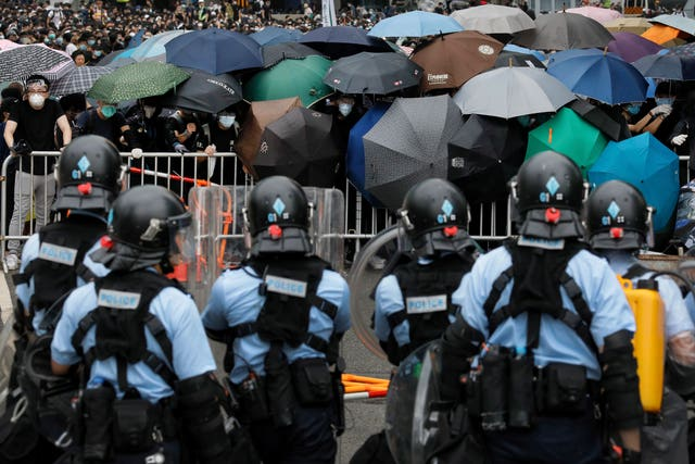 Policemen in anti-riot gear stand watch as protesters use umbrellas to shield themselves
