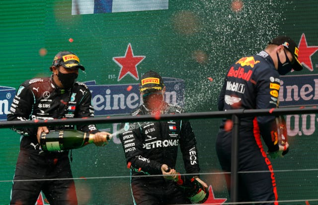 Lewis Hamilton, left, sprays champagne at third-placed Max Verstappen on the podium