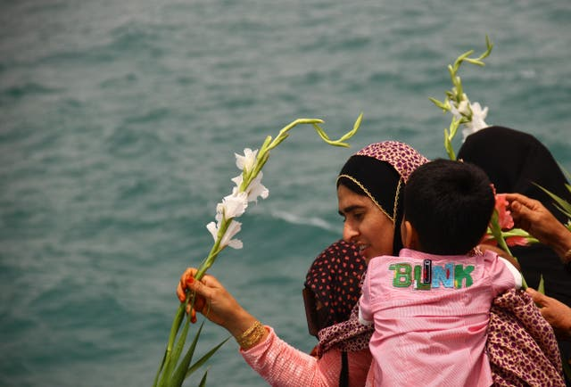 An Iranian woman scatters flowers into the Persian Gulf at the site where an Iranian passenger plane was downed by a US warship, killing all 290 aboard