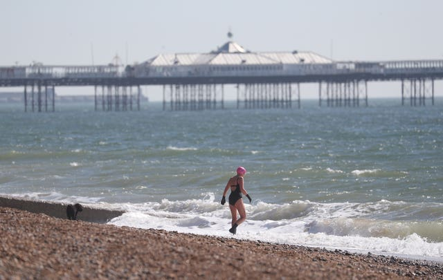 A person goes for a swim in the sea off of Brighton beach (Andrew Matthews/PA Wire)