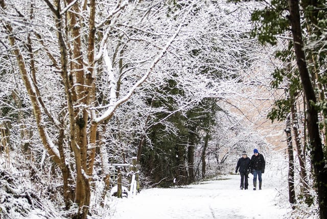 A couple walk through the snow in Auchendinny, Midlothian