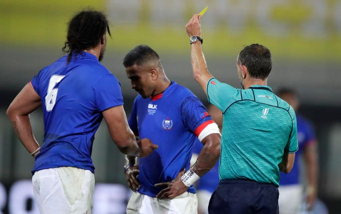 Referee Romain Poite shows Samoa's Rey Lee-lo (centre) a yellow card