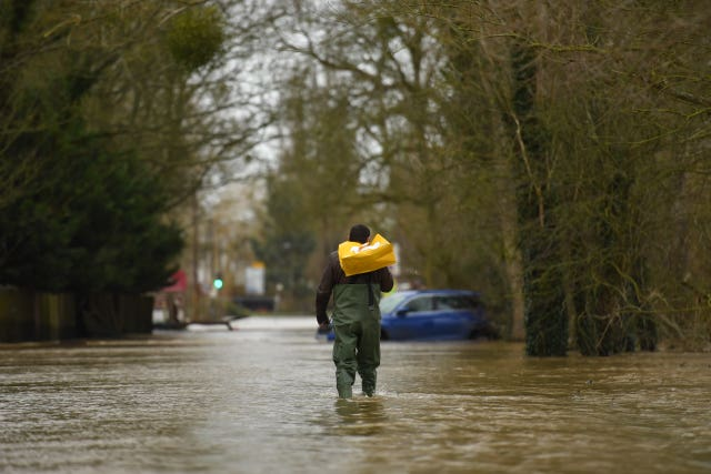 A man wades through floodwater in Upton-upon-Severn, Worcestershire