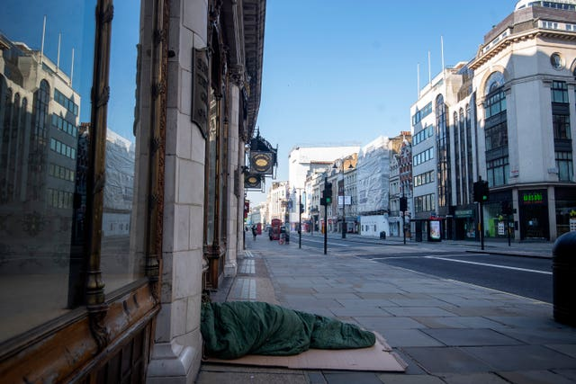 A homeless person lies on the pavement during rush hour on the Strand in Westminster, London (Victoria Jones/PA)
