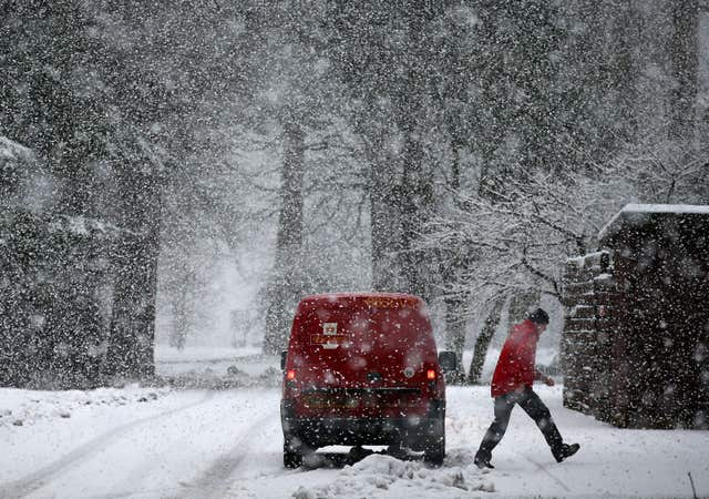 A postman delivers mail in blizzard conditions near Doune, Central Scotland, as the Met Office has issued an amber